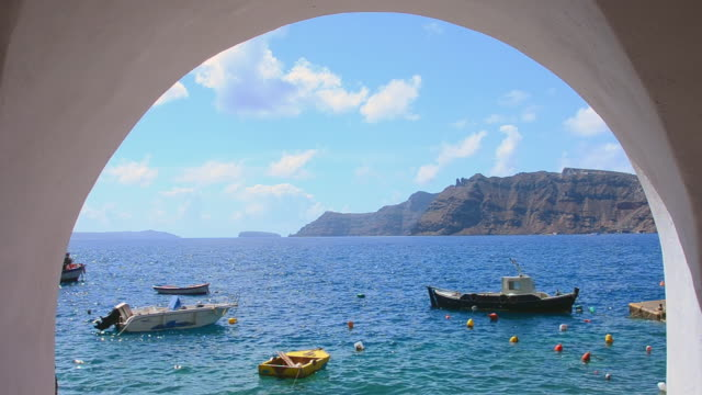 vídeos de stock, filmes e b-roll de ms shot of oia cyclades greek islands boats seen thru arch fishing village below oia greek islands / santorini, greece - oia santorini