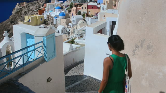vídeos de stock, filmes e b-roll de ms shot of oia cyclades white buildings and steep mountains greek islands beautiful peaceful place greek with asian woman tourist / santorini, greece - oia santorini