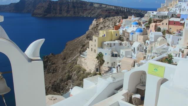 ms pan shot of oia cyclades white buildings, bell and steep mountains greek islands beautiful peaceful place greek / santorini, greece - イア点の映像素材/bロール