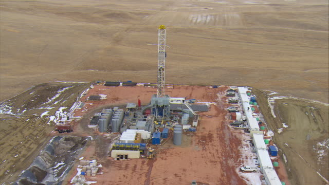 MS AERIAL DS Shot of oil drilling rig at Bakken oil field in snowy fields near Watford City / Watford City, North Dakota, United States