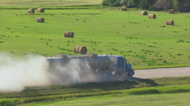 CU AERIAL TS ZO Shot of Oil truck driving on country road along farmland / North Dakota, United States
