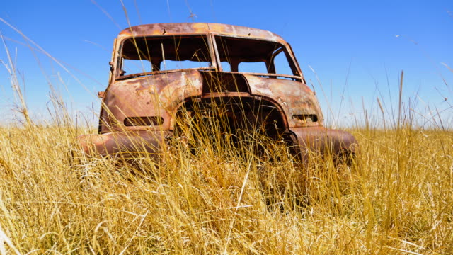 CU T/L LA Shot of old car in field / South Africa