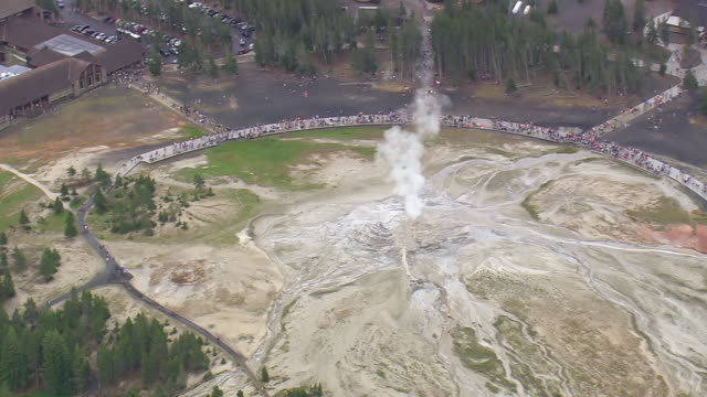 ws aerial shot of old faithful cone geyser and tourist / wyoming, united states - old faithful stock videos & royalty-free footage