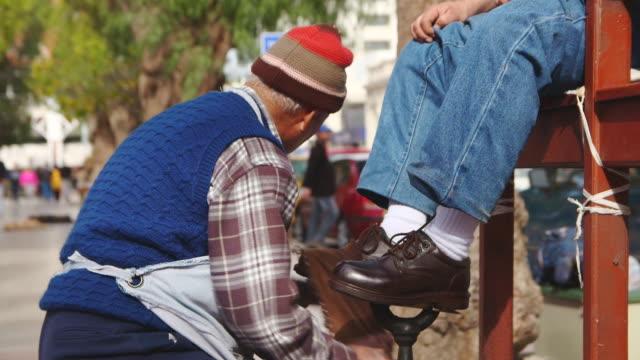 vidéos et rushes de ms shot of old man polishing shoes in city plaza / santiago, chile - chaussures