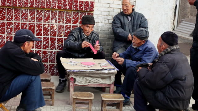 MS Shot of old people are playing bridge card game / Xian, China