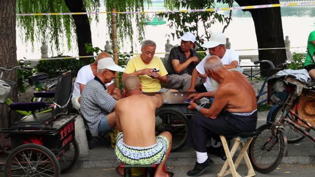 ms shot of old people playing traditional card game at houhai lakes area / beijing, china - mindre än 10 sekunder bildbanksvideor och videomaterial från bakom kulisserna