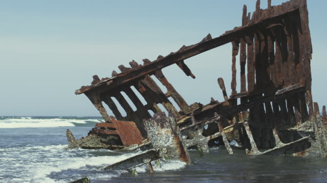 stockvideo's en b-roll-footage met ms slo mo shot of old rusted shipwreck of peter iredale is sunk in high tide off oregon coast / astoria, oregon, united states  - scheepswrak