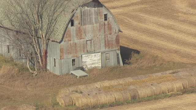 cu aerial zo shot of old white barn with hay bails and pull out to ms in morrison county / minnesota, united states - hay stock videos and b-roll footage
