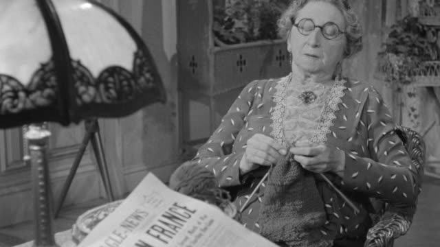 MS PAN Shot of Old woman is sitting hands hold the spindle wool near by news paper