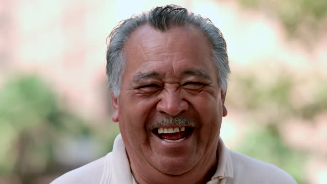 vidéos et rushes de cu shot of older man smiling and laughing really hard and his eyes are happy with content / los angeles, california, united states - latino américain