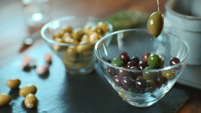 cu slo mo shot of olives being poured into bowl / united kingdom / united kingdom - olive fruit stock videos and b-roll footage