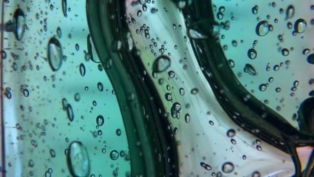 ecu shot of one big bubble rises in a green and yellow color gel substance / tokyo, japan - liquid stock-videos und b-roll-filmmaterial