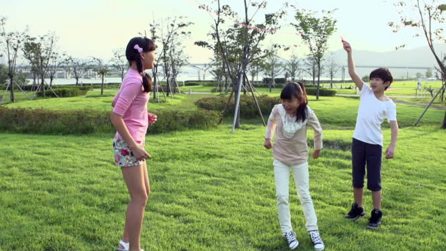 ms slo mo shot of one boy and two girls doing jump rope / seoul, south korea - jump rope stock videos and b-roll footage