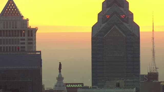 MS AERIAL Shot of One Liberty Place and William Penn statue on top of City Hall building with sunset / Philadelphia, Pennsylvania, United States