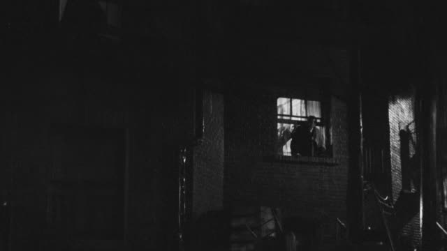 WS Shot of One man entering in house through window with help of ladder at night