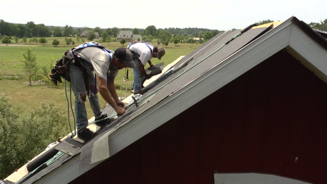 ms shot of one worker moving shingles while another is hammering on roof of red building / chelsea, michigan, united states - provincial reconstruction team stock videos & royalty-free footage