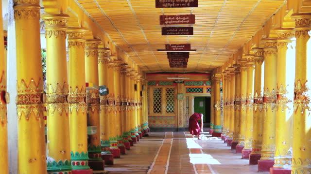 WS Shot of onk in traditional dress in walkway Kha Khat Wain, Kyaung Monastery / Bago, Burma