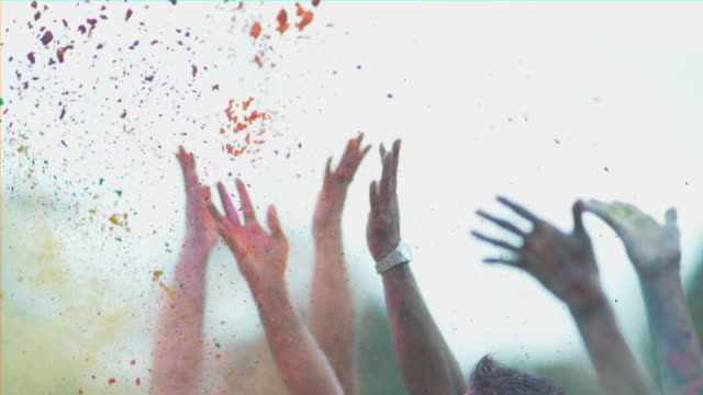 vídeos de stock, filmes e b-roll de shot of only hands throwing holi colors in the air - focus on foreground
