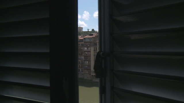 ms shot of opening window shutters and city across river  / florence, tuscany, italie - persiana caratteristica architettonica video stock e b–roll