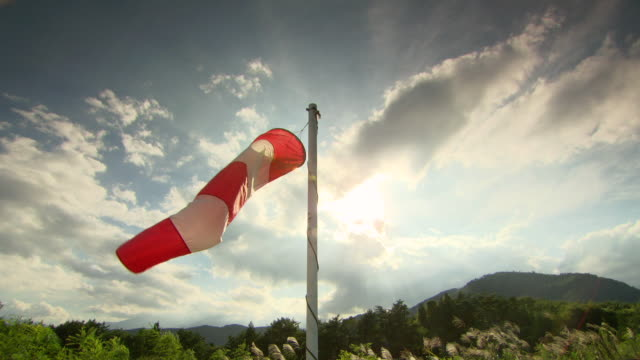 vídeos de stock, filmes e b-roll de ws shot of orange and white windsock, blowing in wind with mountains / fukashima, tohoku, japan - biruta