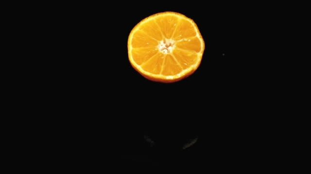 CU SLO MO Shot of Orange, citrus sinensis, Slice Falling on Water and splashing against Black Background / Calvados, Normandy, France
