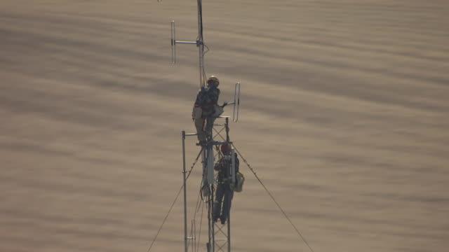 vídeos y material grabado en eventos de stock de cu aerial shot of orbit around cell phone tower workers in steele county / minnesota, united states - transmisión