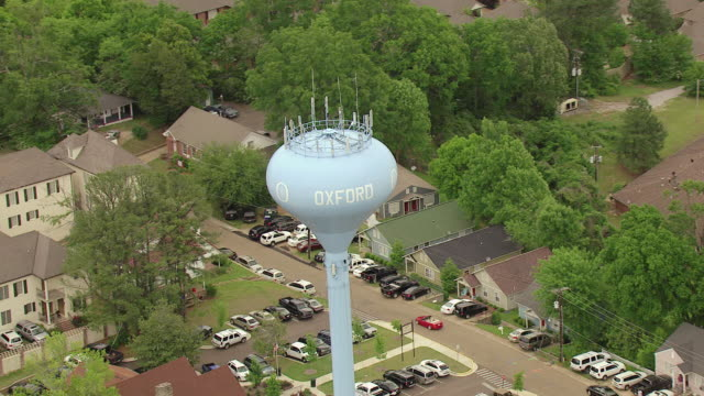 ms aerial shot of orbit around oxford blue water tower surrounded by houses / oxford, mississippi, united states - 牛津 個影片檔及 b 捲影像