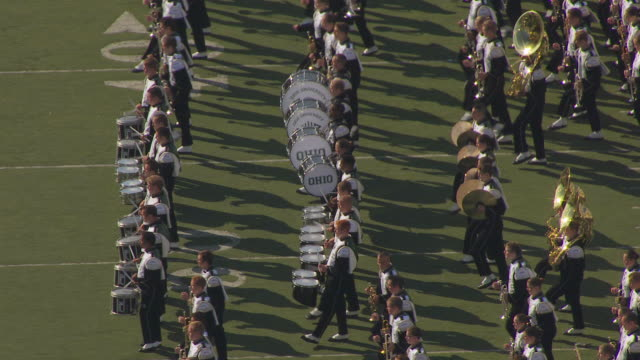 ms ts aerial shot of orbit around percussion players and brass players during marching band practice for ohio university homecoming parade / athens, ohio, united states - banda che marcia video stock e b–roll