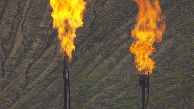 CU AERIAL TS ZO Shot of Orbit flames and pull out to reveal oil well / Watford City, North Dakota, United States
