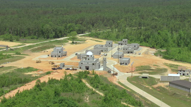 MS AERIAL Shot of orbit Middle Eastern practice village with buildings made of cement and mosque with whole town at Camp Shelby military post / Mississippi, United States