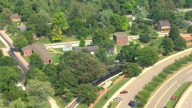MS AERIAL SHot of  orbit Thomas Edisons Menlo Park Complex with black train passing by / Dearborn, Michigan, United States