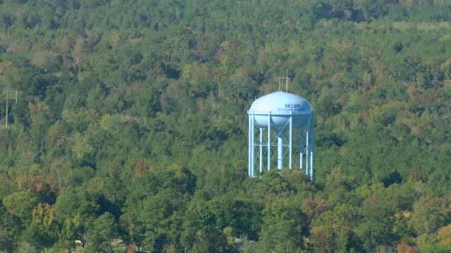 stockvideo's en b-roll-footage met ms aerial shot of orbit water tower sign surrounded by trees / selma, alabama, united states - alabama