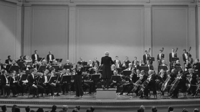 ws shot of orchestra playing on stage over heads of audience - classical stock videos & royalty-free footage