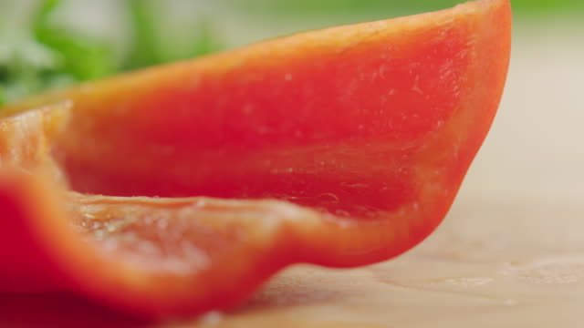 ecu r /f shot of organic red bell pepper on kitchen cutting board, section of pepper is cut into several strips with steel knife / los angeles, california united states - bell pepper stock videos & royalty-free footage