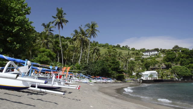 MS Shot of Outrigger fishing boats standing on palm tree beach with few beach houses at Asia / Candi, Dasa Bali, Indonesia