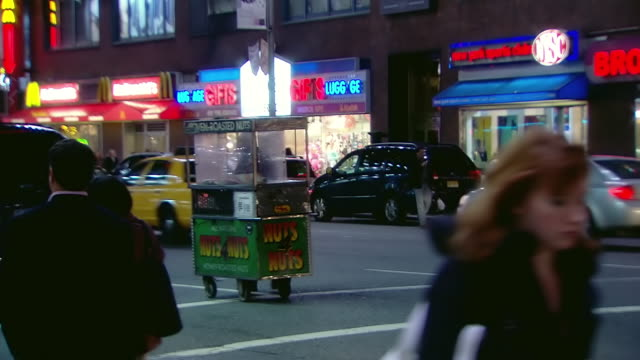 CU Shot of Oven roasted vendor cart moving down street at night / New York, United States