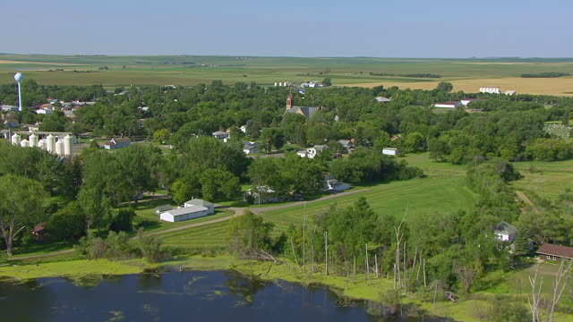 MS AERIAL LA TU Shot of Over fields and approaching town to reveal buildings and St Peter and Paul church / Strasburg, North Dakota, United States