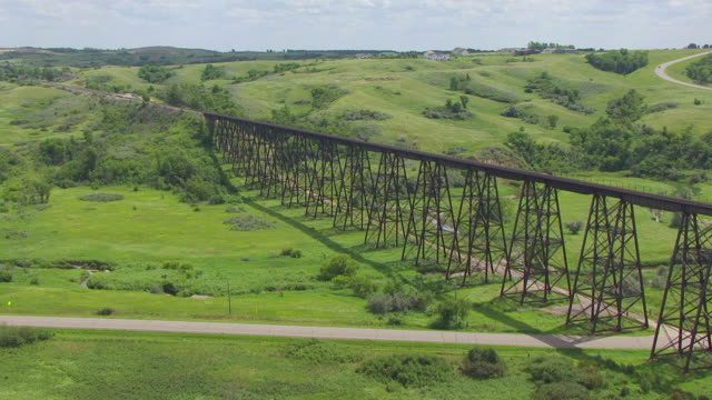 MS AERIAL LA TU TS Shot of Over grass to reveal Gasman Coulee Railroad Trestle and pass over trestle / Minot, North Dakota, United States