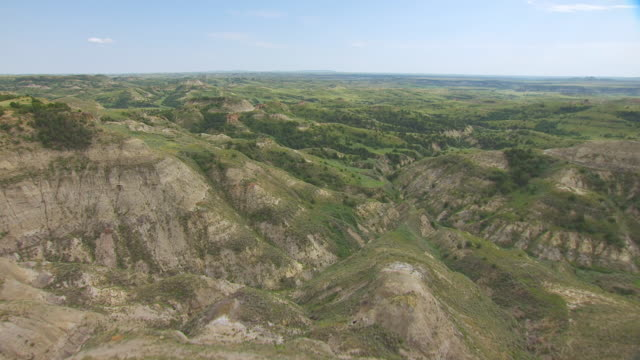 MS AERIAL TD TU Shot of Over ridge of badlands at Theodore Roosevelt National Park / North Dakota, United States