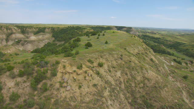 MS AERIAL Shot of Over ridge of badlands at Theodore Roosevelt National Park / North Dakota, United States