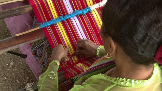 CU HA Shot of Over shoulder for woman weaving beautiful garment / Soe, Mt. Mutis, West Timor Indonesia