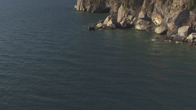 ms aerial shot of over water to reveal split rock lighthouse / minnesota, united states - lago superiore video stock e b–roll