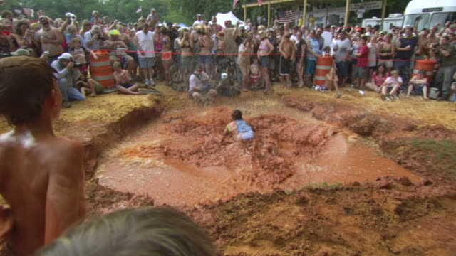 ws shot of overweight woman throwing herself into mud pit making big splash during competition at summer redneck games / dublin, georgia, united states - mud stock videos & royalty-free footage