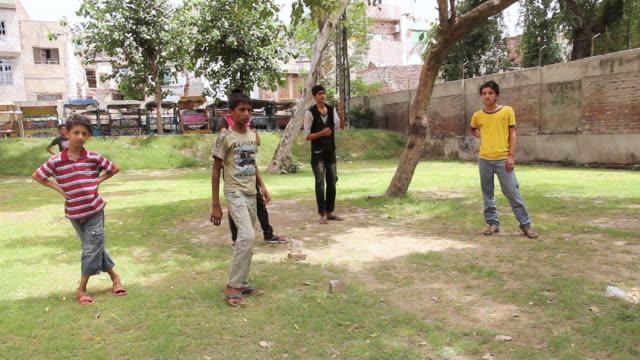 vidéos et rushes de shot of pakistani kids playing cricket / old city of lahore, punjab, pakistan - lahore pakistan