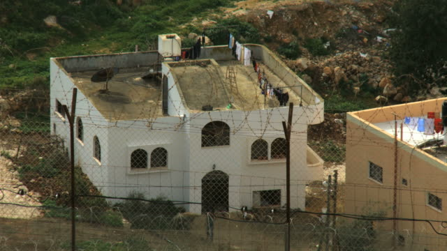 ms shot of palestinian house with israeli separation wall in front / ma'ale gilboa, samaria, israel - recinzione video stock e b–roll