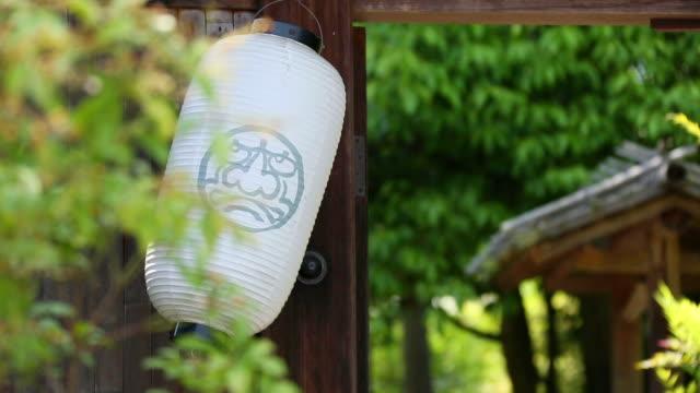 vídeos y material grabado en eventos de stock de cu shot of paper lantern shaking by wind / arashiyama, kyoto, japan - letrero de tienda