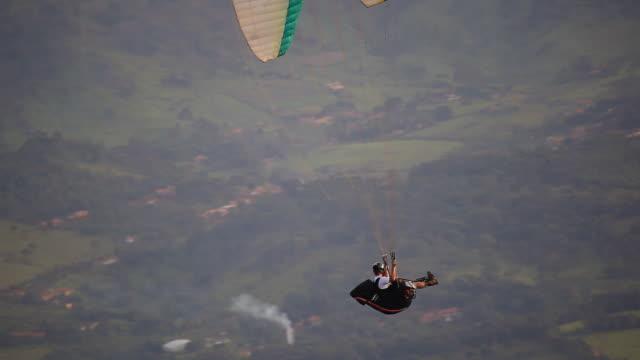 ws shot of para glider flying in air over mountain hill / belo horizonte, minas gerais, brazil - horizonte stock videos & royalty-free footage