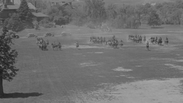 ws shot of parade with cadets on horseback in formation on empty field - arbeitstier stock-videos und b-roll-filmmaterial