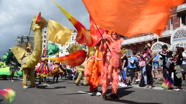 Shot of paraders dressed up in bright coloured animal costumes in the Brighton Gay Pride Parade 2017 in slow motion