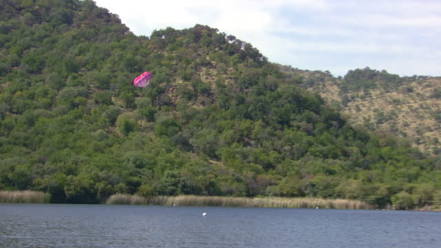 MS TS ZO SLO MO Shot of Paraglider being pulling behind speed boat and Sun City Dam / North West Province, South Africa